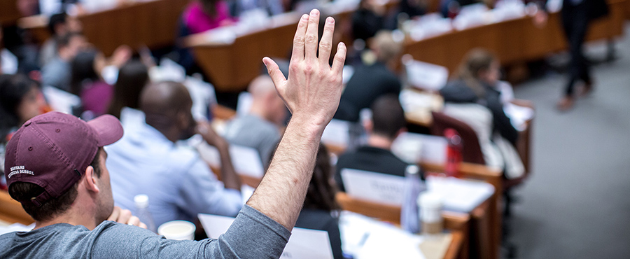 Student raises his hand in an HBS classroom